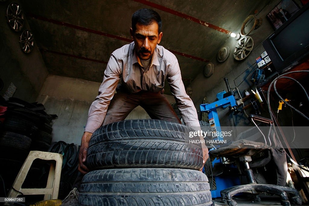 Abu Haidar works on tires at his tire repair shop, where he transforms unused tires into furniture, in the Diwaniya village, east of the holy Iraqi city of Najaf, on February 13, 2016. / AFP / HAIDAR HAMDANI