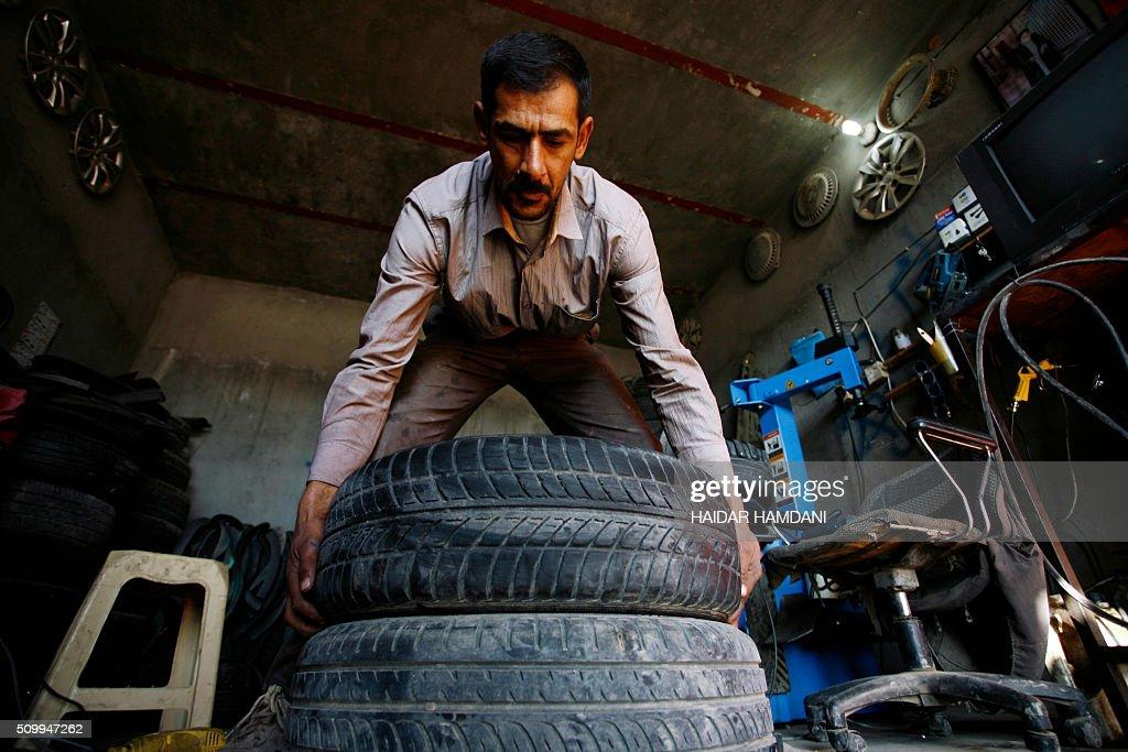 Abu Haidar works on tires at his tire repair shop, where he transforms unused tires into furniture, in the Diwaniya village, east of the holy Iraqi city of Najaf, on February 13, 2016. / AFP / HAIDAR HAMDANI