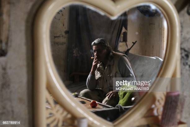 TOPSHOT Abu Haitham a 57yearold rebel fighter from the Free Syrian Army's 18 March Division sits in a building on the front line in the southern city...