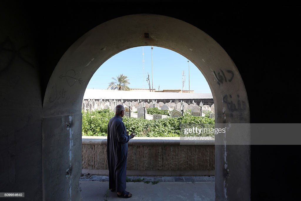 Abu Qassem, a local who helped evacuate the wounded in the bombing on a shelter in Ameriya in 1991, prays over the tombs of the victims at the site of the shelter in Baghdad on February 13, 2016. The shelter was bombed by the allied forces during the 1991 Gulf War. Approximately 400 Iraqis perished in the attack. / AFP / SABAH ARAR