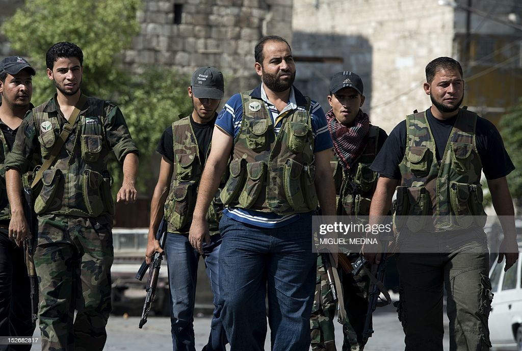Abu Riad a defecting army officer who heads a brigade in Aleppo's old town walks with members of his brigade in the northern Syrian city on September...