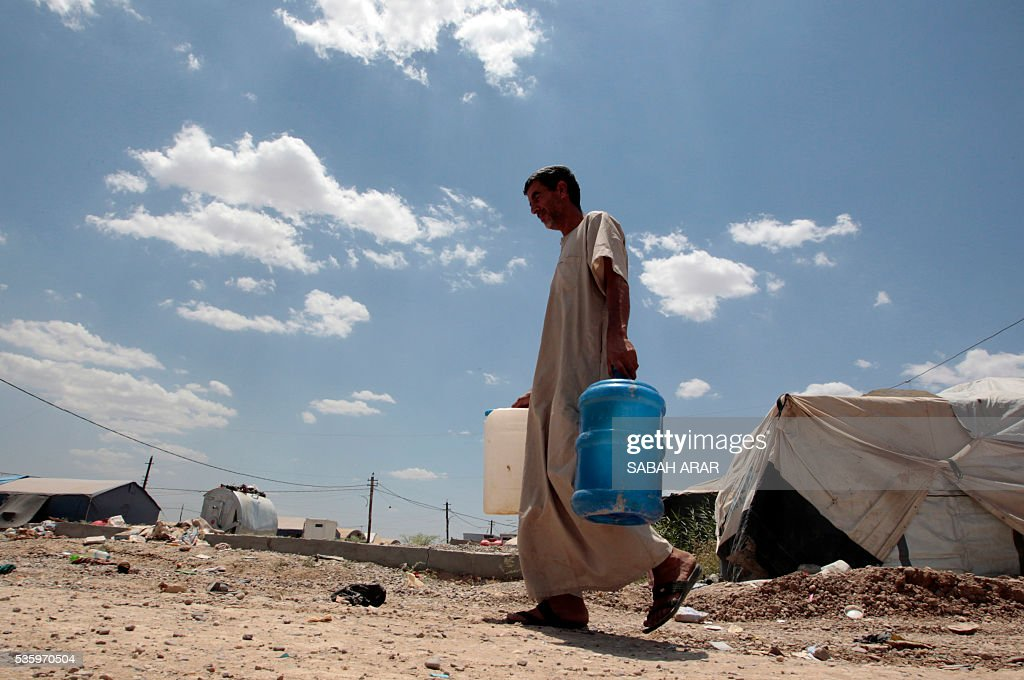 Abu Shiab carries water on May 31, 2016 at the Alexanzan camp in the Dora neighbourhood on the southern outskirts of Baghdad where he is taking shelter with his family after they were displaced from the Jbeil, a village near the embattled Iraqi city of Fallujah due to clashes between pro-government forces and the Islamic State (IS) group. Only a few hundred families have managed to slip out of the Fallujah area ahead of the assault on the city, with an estimated 50,000 civilians still trapped inside, sparking fears the jihadists could try to use them as human shields. ARAR