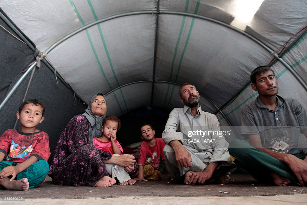 Abu Shiab (C-R) sits with his family in a tent on May 31, 2016 at the Alexanzan camp in the Dora neighbourhood on the southern outskirts of Baghdad after they were displaced from the Jbeil, a village near the embattled Iraqi city of Fallujah, due to clashes between pro-government forces and the Islamic State (IS) group, Only a few hundred families have managed to slip out of the Fallujah area ahead of the assault on the city, with an estimated 50,000 civilians still trapped inside, sparking fears the jihadists could try to use them as human shields. ARAR
