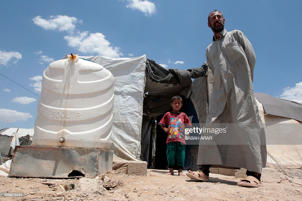 Abu Shiab (R) stands outside a tent on May 31, 2016 at the Alexanzan camp in the Dora neighbourhood on the southern outskirts of Baghdad where he is taking shelter with his family after they were displaced from the Jbeil, a village near the embattled Iraqi city of Fallujah due to clashes between pro-government forces and the Islamic State (IS) group. Only a few hundred families have managed to slip out of the Fallujah area ahead of the assault on the city, with an estimated 50,000 civilians still trapped inside, sparking fears the jihadists could try to use them as human shields. ARAR