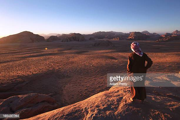 Abu Sultan a Bedouin guide looks over the desert of Wadi Rum at sunset on March 28 2013 in Wadi Rum Jordan