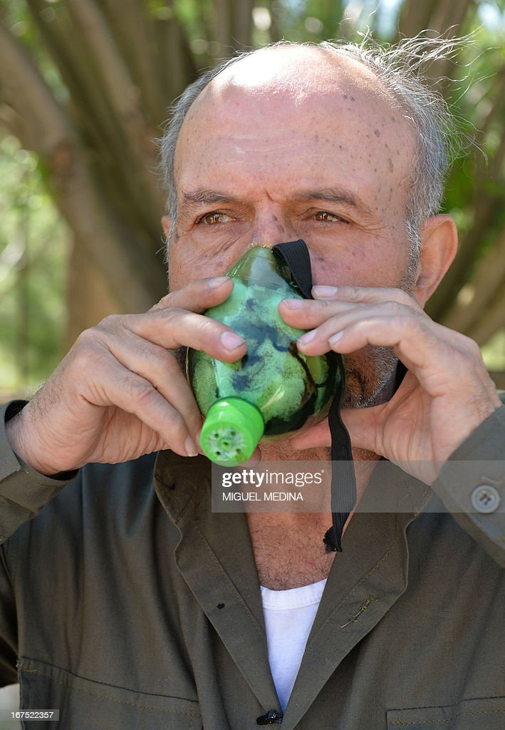 Abu Tarek, 74, retired officer from the army, member of the Al-Ezz bin Abdul Salam brigade shows how to use a mask that he made using notably a squeeze bottle, coal, cotton, gauze, cola, cardboard in order to protect himself from chemical weapons on April 26, 2013 in the Latakia province, western Syria. British Prime Minister said on April 26, 2013 that growing evidence of the use of chemical weapons by the Syrian regime was 'extremely serious'.