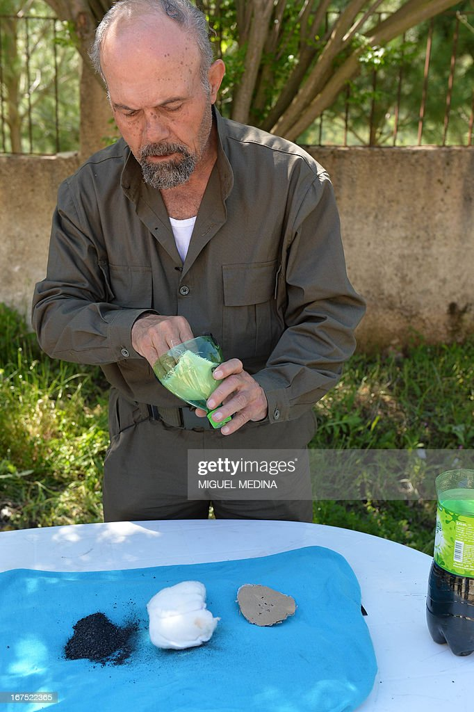 Abu Tarek, 74, retired officer from the army, member of the Al-Ezz bin Abdul Salam brigade shows how to make a mask using notably a squeeze bottle, coal, cotton, gauze, cola, cardboard in order to protect himself from chemical weapons on April 26, 2013 in the Latakia province, western Syria. British Prime Minister said on April 26, 2013 that growing evidence of the use of chemical weapons by the Syrian regime was 'extremely serious'.