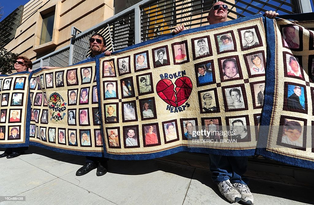 Abuse victim Jorgen Olsen (R) and supporter Glenn Gorospa (L) hold quilts bearing portraits of abused children while gathered outside the Cathedral of Our Lady of the Angels in Los Angeles, California, on February 1, 2013, one day after the release of personnel files of priests accused of sexual misconduct. The archbishop of Los Angeles Jose Gomez stripped his predecessor, retired Cardinal Roger Mahony, of all church duties on January 31. In all, 124 files were released on the Los Angeles archdiocese's website, listed by priests' names, including 82 containing information on allegations of childhood sexual abuse. AFP PHOTO / Frederic J. BROWN
