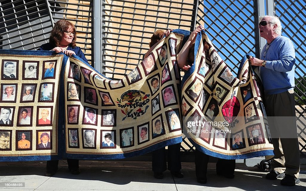 Abuse victims Jim Robertson (R) and Rita Milla (L) are joined by supporters holding quilts bearing the portraits of abused children while gathered outside the Cathedral of Our Lady of the Angels in Los Angeles, California, on February 1, 2013, one day after the release of personnel files of priests accused of sexual misconduct. The archbishop of Los Angeles Jose Gomez stripped his predecessor, retired Cardinal Roger Mahony, of all church duties on January 31. In all, 124 files were released on the Los Angeles archdiocese's website, listed by priests' names, including 82 containing information on allegations of childhood sexual abuse. AFP PHOTO / Frederic J. BROWN