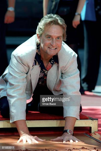Academy Award winning actor Michael Douglas places his hands in cement during a ceremony honoring him at the worldfamous Chinese Theatre 10 September...