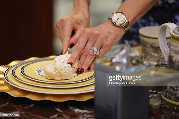 Academy chairman Jennie HallamPeel teaches debutantes the correct way to cut scones during the London Season Academy's first etiquette social and...