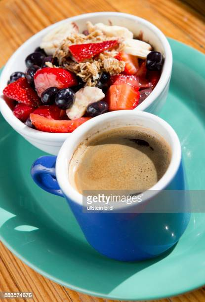 Acai bowl with banana and strawberries next to a coffee