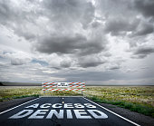 Access denied is painted on a long rural road that comes to an abrupt end. A construction barrier serves notice the one has come to the end of the road.