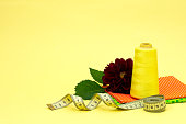 Yellow thread green orange fabric centimeter tape accessories for embroidery flower burgundy on a bright background'n