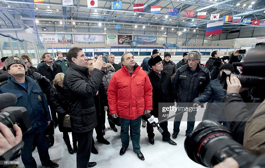 Accompanied by officials and journalists Russia's Emergencies Minister Vladimir Puchkov (C) visits a local sport centre in the Urals city of Chelyabinsk, on February 15, 2013, as he inspected the damage caused by a shockwave from a meteor. The unpredicted meteor strike in central Russia that left today hundreds of people injured, left some Russian officials calling for the creation of a global system of space object defence.