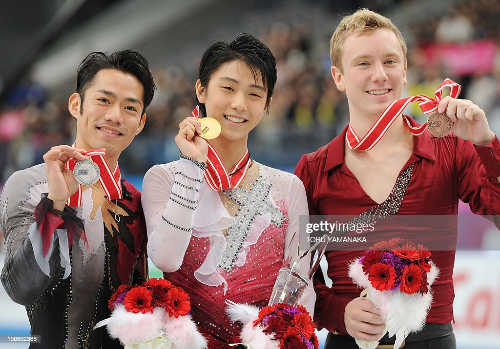 Accompanied by second placed Daisuke Takahashi (L) of Japan and third placed Ross Miner (R) of the US, Yuzuru Hanyu (C) of Japan poses for photographers during the awarding ceremony for the men's event in the NHK Trophy, the last leg of the six-stage ISU figure skating Grand Prix series, in Rifu, northern Japan, on November 24, 2012. AFP PHOTO/Toru YAMANAKA