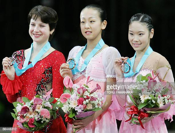 Accompanied by secondplaced Irina Slutskaya of Russia and thirdplaced Yukari Nakano of Japan Mao Asada of Japan shows her gold medal during an...