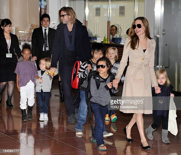 Accompanied by their six children US movie stars Brad Pitt and Angellina Jolie appear before photographers upon their arrival at Haneda Airport in...