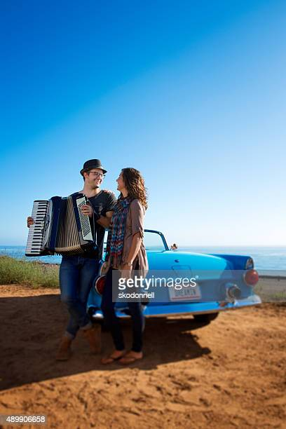 Accordian Couple Laughing by a Blue Convertible