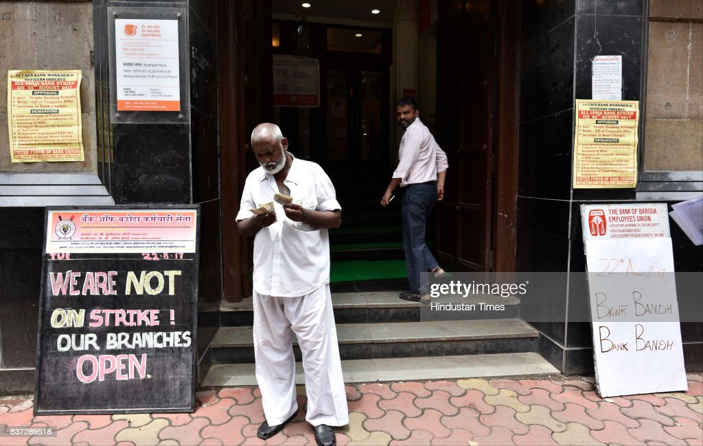 Account holder counting his cash outside Bank of Baroda of Fort which displays both board of strike and Bank is open on August 22, 2017 in Mumbai, India. Normal banking operations have been hit as public sector bank employees went on a one-day nationwide strike today to protest against the government's proposed consolidation move, besides raising other demands.