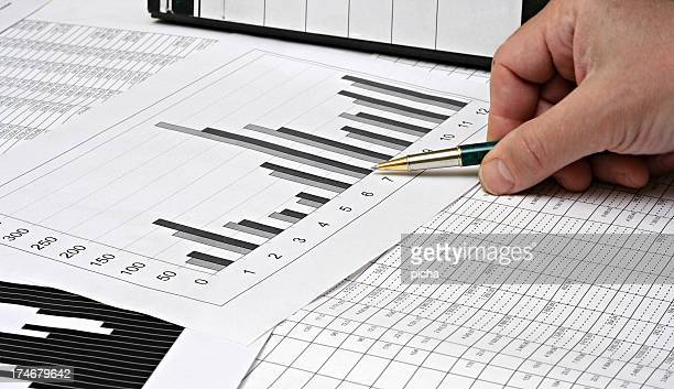 Accountant analyzing a graph and data using a pen