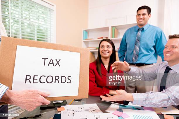 Accountants collaborate on income tax returns. Box foreground.