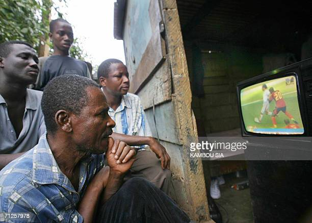 Ghanaians watch a tv sporting the Angola versus Iran world cup football match 21 June 2006 in their room in a poor area of Accra AFP PHOTO / KAMBOU...