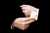 man with ace card hidden under sleeve isolated on blackac