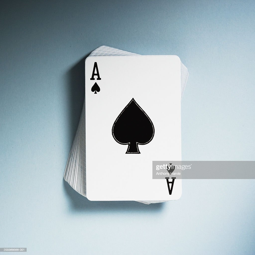 Ace of Spades on top of pack of playing cards, close-up, elevated view : Stock Photo