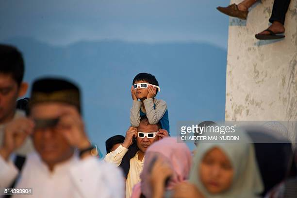 Acehnese people watch the total solar eclipse in Banda Aceh on March 9 2016 A total solar eclipse swept across the vast Indonesian archipelago on...