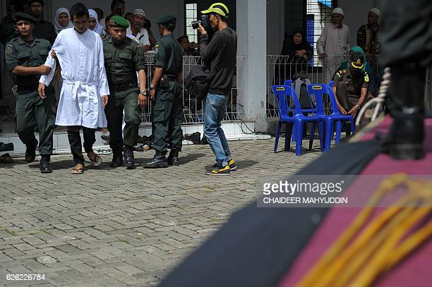 Acehnese religious officers guard a man who will receive 100 lashes of the cane for having sex outside marriage which is against Sharia law in Banda...
