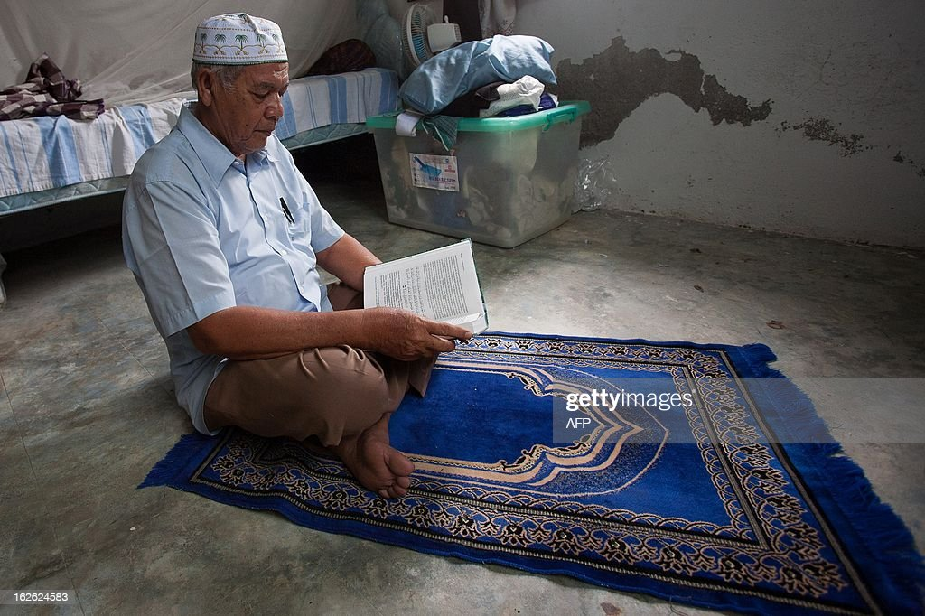 Acehnese Sayed Hasan reads an Islamic book at his house in Banda Aceh on February 25, 2013. Hasan said on February 25 he had won a rare victory against a noisy mosque, despite being forced to withdraw legal action after an angry mob threatened to kill him. Complaints against the loud speakers issuing the call to prayer have been met with extreme opposition in Indonesia, the world's biggest Muslim-majority nation that is home to about 800,000 mosques.