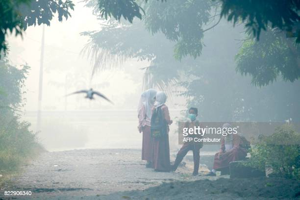 TOPSHOT Acehnese schoolchildren clad in masks wait for their bus to school while shrouded in thick smoke due to peat forest fires in Meulaboh Aceh...