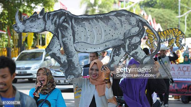 Acehnese students hold up cutouts of endangered animals during a rally as part of a 'Global March' for Rhinos Elephants Tigers and Orangutans in...