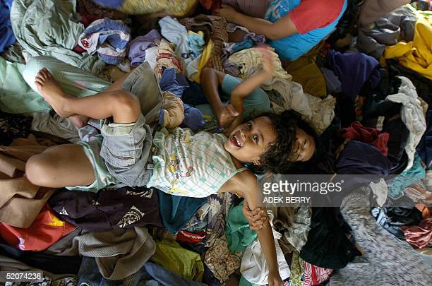 Acehnese tsunami disaster surviving children play on the clothes they got as donation at their refugee camp in Banda Aceh 28 January 2005 Indonesia...