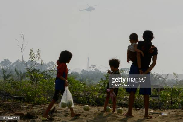 TOPSHOT Acehnese villagers watch as a helicopter drops water over a peat forest fire in Meulaboh Aceh province on July 26 2017 Some 35 fire hotspots...