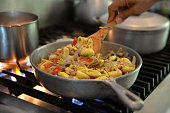 Jamaican national dish, ackee and saltfish, cooked in a traditional dutch pan over a flame.