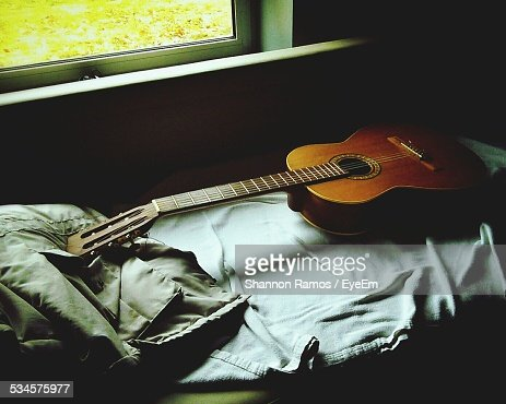Acoustic Guitar On Bed At Home