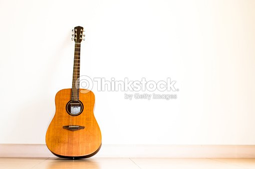 Acoustic Guitar Standing In White Room Background Stock Photo