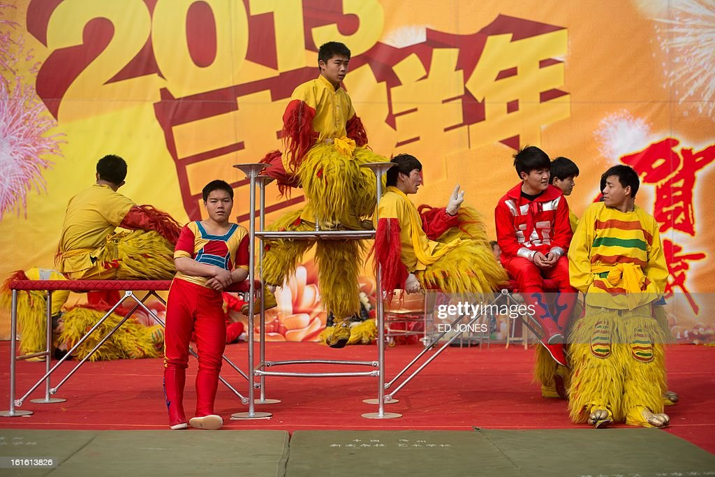 Acrobats and lion dancers wait on stage prior to a performance at a temple fair at Longtan park in Beijing on February 13, 2013. A billion-plus Asians are ushering in the lunar Year of the Snake with a week of festivities. AFP PHOTO / Ed Jones