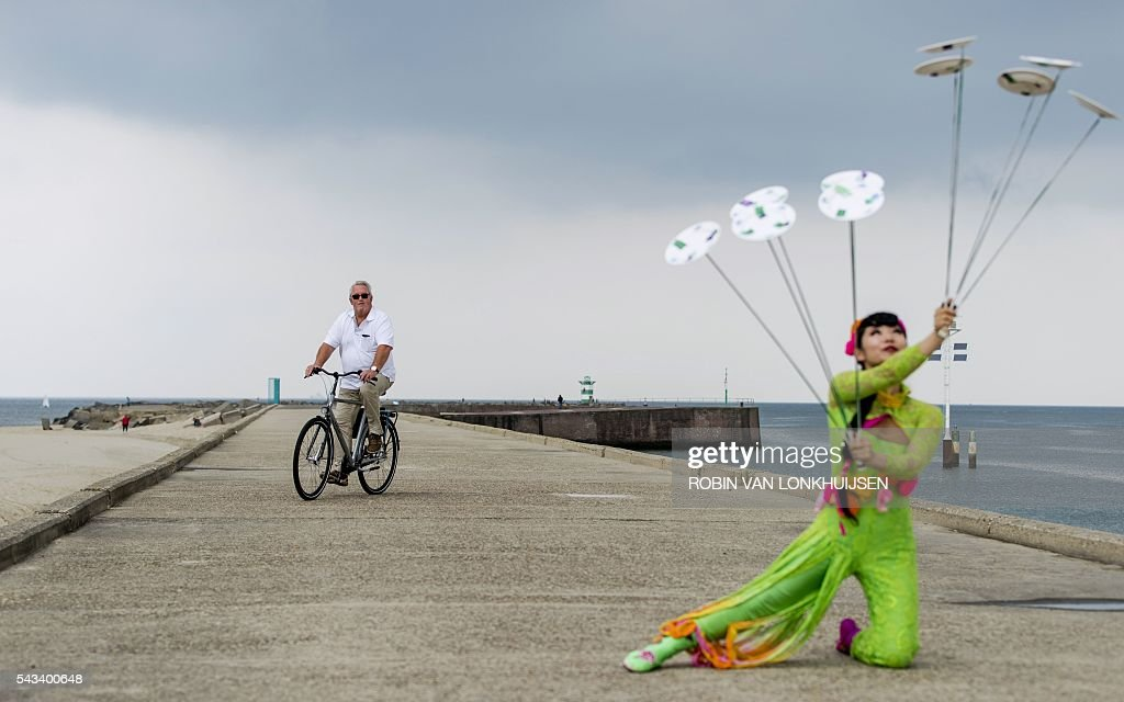 TOPSHOT - Acrobats of the China national Acrobatic Troupe take part in a presentation at Scheveningen harbour, the Netherlands, on June 28 2016. Scheveningen will host their show Splendid from June 29 to July 10. / AFP / ANP / Robin van Lonkhuijsen / Netherlands OUT