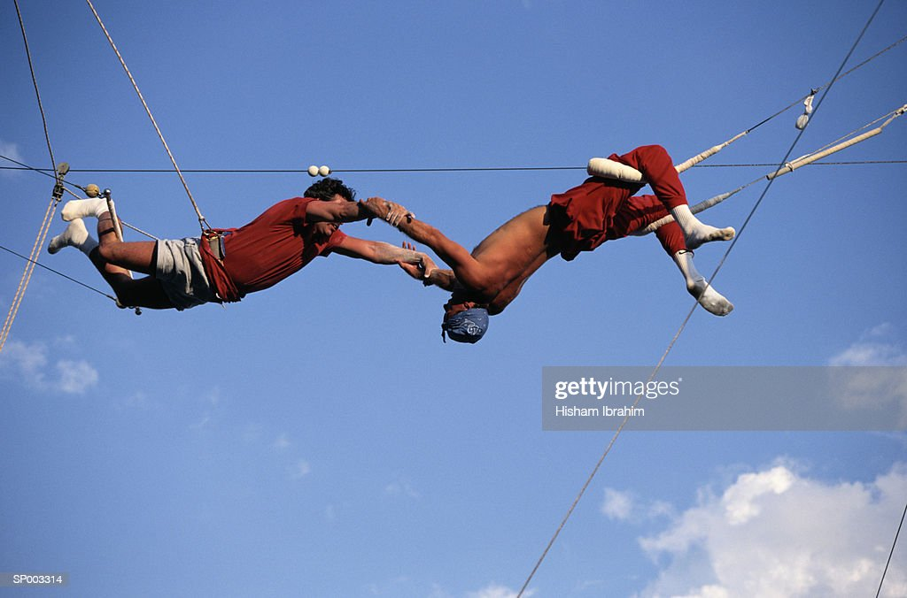 Acrobats practicing on trapeze, low angle view