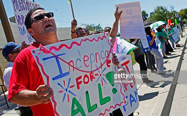 Across the street Raul Razo holds a sign against deportation as protesters from both sides voice their differences near the Santa Maria Courthouse...