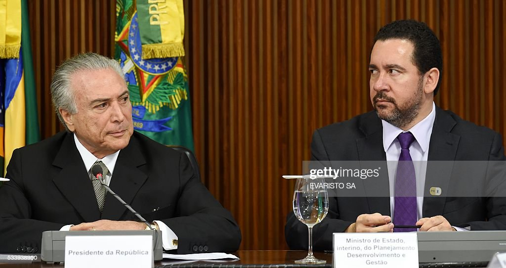 Acting Brazilian President Michel Temer (L) and acting Planning Minister Dyogo Oliveira during a meeting held with allied party leaders in Congress to present their economic measures at the Planalto Palace in Brasilia on May 24, 2016. / AFP / EVARISTO SA