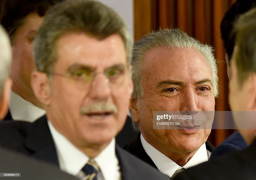 Acting Brazilian President Michel Temer (R) and Romero Juca, a former minister of planning who left the government due to allegations of involvement in attempts to block investigations of corruption at Petrobras, during a meeting held with allied party leaders in Congress to present Temer's economic measures at the Planalto Palace in Brasilia on May 24, 2016. / AFP / EVARISTO SA