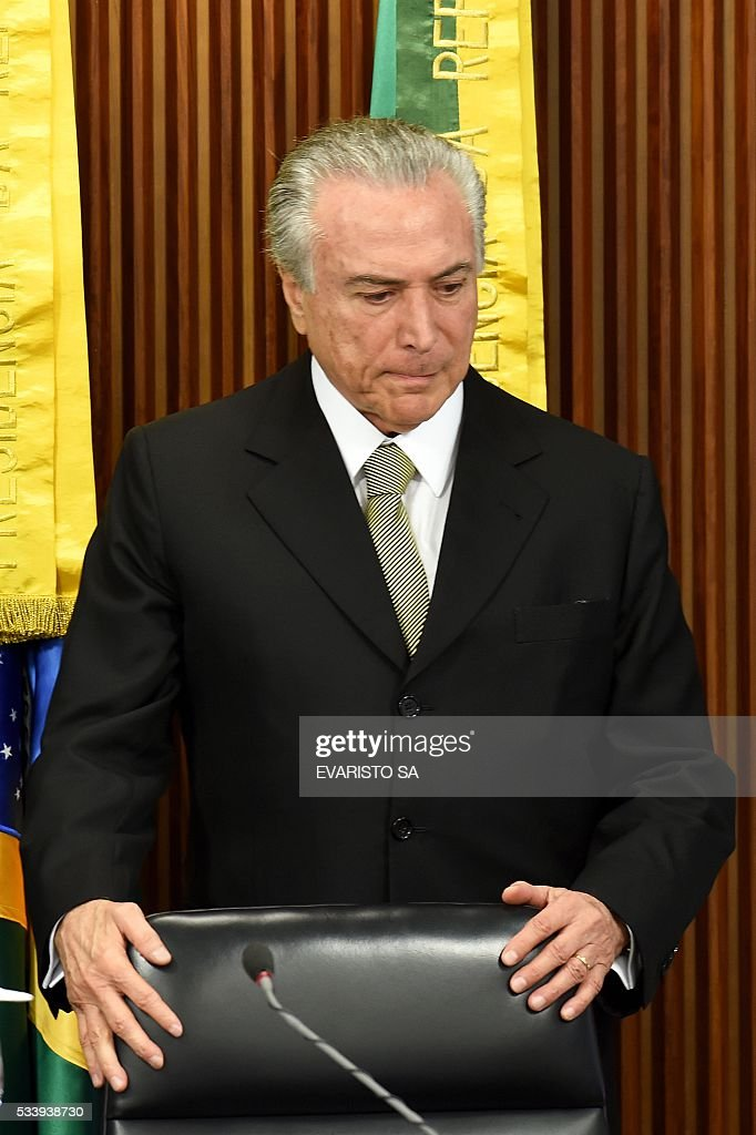 Acting Brazilian President Michel Temer arrives at a meeting held with allied party leaders in Congress to present his economic measures at the Planalto Palace in Brasilia on May 24, 2016. / AFP / EVARISTO SA