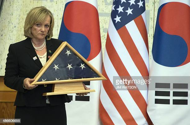 Acting Chief of Protocol for the US Rosemarie Paulie holds up a shadow box containing the US flag that flew over the White House on the day the Sewol...