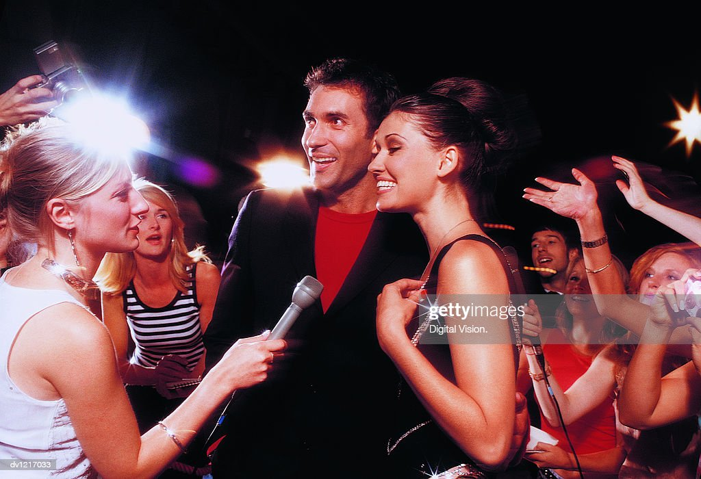 Acting Couple Being Interviewed by a TV Reporter in Front of a Group of Fans Taking Photographs : Stock Photo
