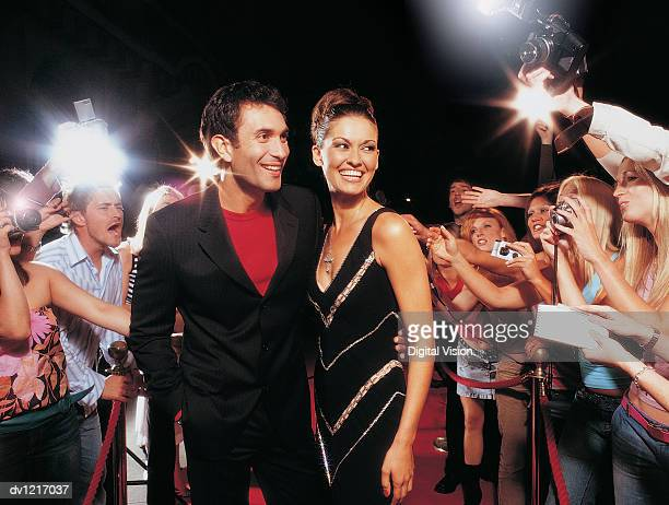 Acting Couple Being Photographed Standing on a Red Carpet