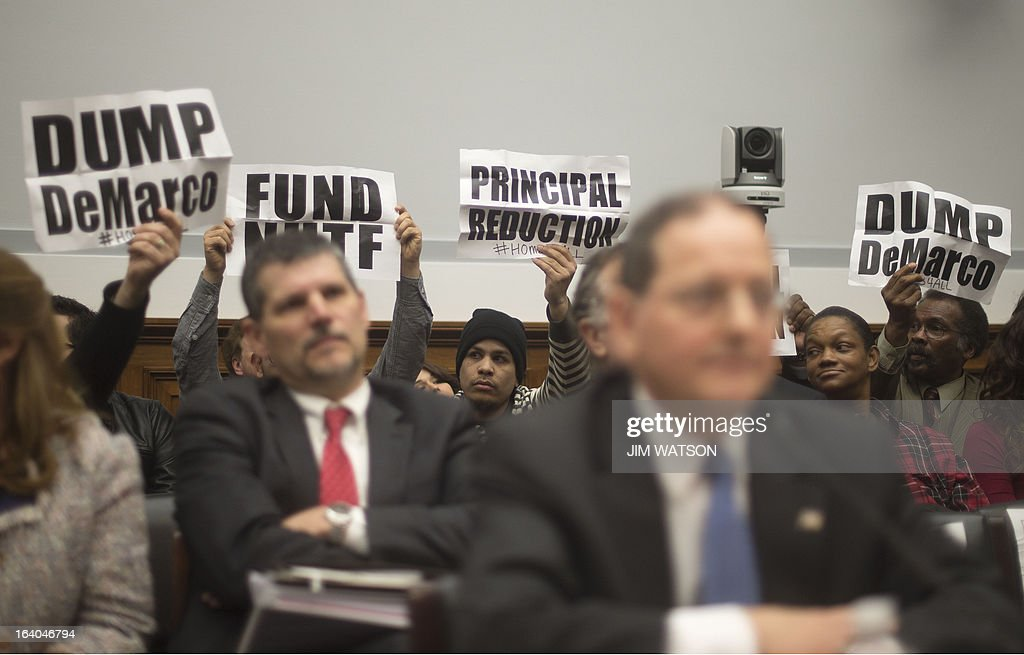 Acting Director of the Federal Housing Finance Agency, the conservator for Fannie Mae and Freddie Mac, Edward J. DeMarco (C) pauses his testimony as demonstrators hold up placards in the background during a hearing on 'Sustainable Housing Finance' before the House Financial Services Committee in Washington, DC, March 19, 2013. AFP PHOTO/Jim WATSON